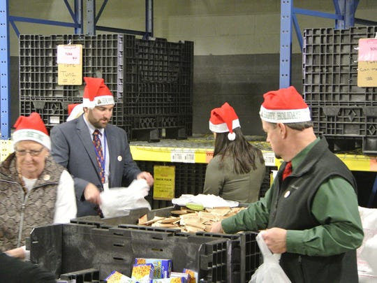 From left, Steuben County Legislator Carol Farratella, Hornell Superintendent Jeremy Palotti, and Bill Caudill (far right), Steuben Youth Bureau Coordinator package food times for the  Food bank of the Southern Tier's BackPack program Tuesday.