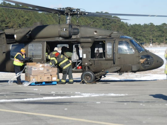 Members of the Crisfield Fire Company assist in loading one of the two Black Hawk helicopters from the Virginia National Guard on Saturday, Jan. 6.  The food will be delivered to Tangier Island, which is iced in.