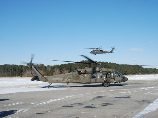 Two Black Hawk helicopters arrive at the Crisfield airport Saturday, Jan. 6, where they were set to ferry cargo to iced-in Tangier Island.