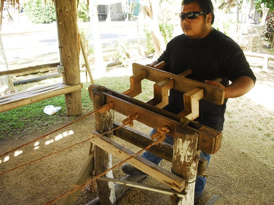A staff member at Historic Inalahan demonstrates the biridot, which twists fiber together to make rope.