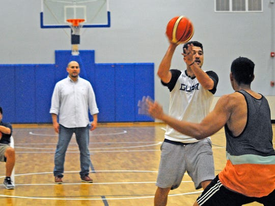 Willie Stinnett, with ball, looks for an opening over Ben Borja during Team Guam practice at the Guam Basketball National Training Center in Tiyan on June 13. At rear are Team Guam head coach E.J. Calvo, standing, and assistant coach Danny Payumo.