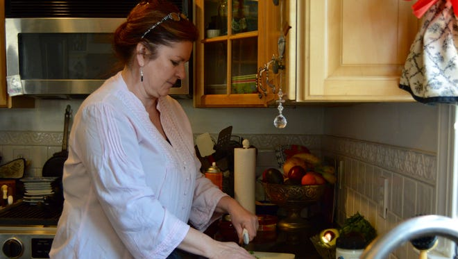 Malia Ricks chops fresh cilantro in her Berlin home. Ricks is the chef and owner of Malia's Cafe in Ocean City.