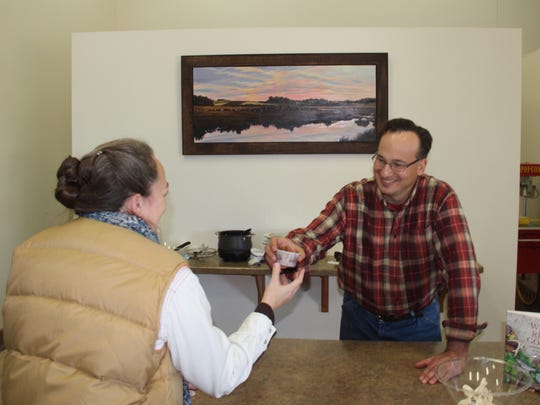 Wild game chef and book author John Motoviloff of Madison hands a sample of venison chili to Heather Bassett of Mayville at a game and fish cooking seminar at Horicon Marsh Education and Visitor Center in Horicon.