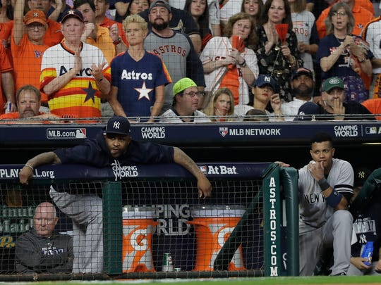 New York Yankees' CC Sabathia, left, and Starlin Castro watch from the dugout during the eighth inning of Game 7 of baseball's American League Championship Series against the Houston Astros Saturday, Oct. 21, 2017, in Houston.