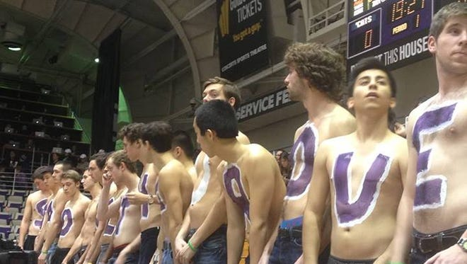 """Northwestern University students painted """"Stand With Purdue"""" in purple and white on their chests during the Purdue men's basketball game at Northwestern, Tuesday, Jan. 21, 2014, after a Purdue student was shot and killed on the Purdue University campus around noon."""