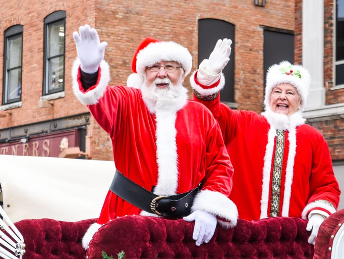 Mr. and Mrs. Claus wave to attendees of the 34th Annual