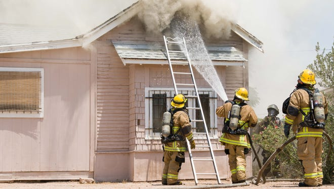 Phoenix Fire Department Engine 4 tries to contain a house fire south of Interstate 10 near 11th Street at Moreland on June 19, 2017. The downtown Phoenix temperature was rising in triple digits.