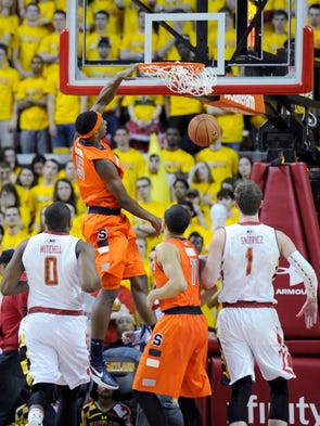 Syracuse forward C.J. Fair (5) dunks against Maryland forward Evan Smotrycz (1) and Charles Mitchell (0) during the second half of an NCAA college basketball game, Monday, Feb. 24, 2014, in College Park, Md. Syracuse won 57-55. Also seen is Syracuse guard Tyler Ennis (11).