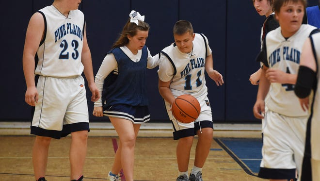 Pine Plains' Tyler Parrotte, center right, gets helped down the court by cheerleader Haleigh Rockefeller, center left, during Thursday's Unified Basketball game against Rondout. Parrotte, who is almost totally blind, scored a basket during the game.