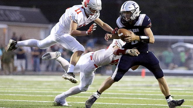 Sandy Valley's Pacey Baum (left) and Brandon Loveless take down Fairless quarterback Ethan Brindley during the second quarter of the 2019 season opener.
