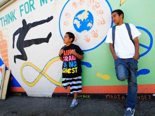 In this May 10, 2011, file photo, Van Buren Elementary school seventh grade students Daniel Mayen, left, and Victor Gonzalez, right, take a break at school in Stockton, Calif.