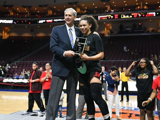 Jeff Herd, commissioner of the Western Athletic Conference, gives Kamira Sanders a plaque for earning MVP honors in the WAC Tournament.