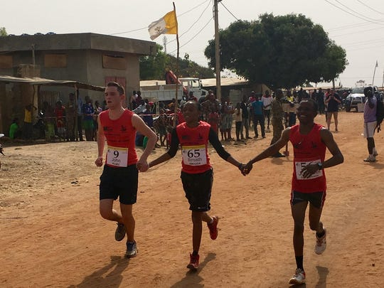 Salesianum senior Jack Villec `17, left, finishes the Salesian Marathon in Parakou, Benin, hand in hand with two local runners.