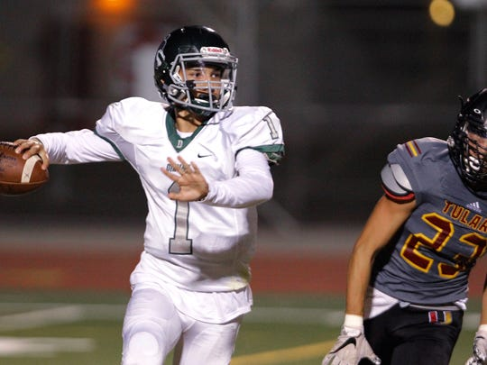 Dinuba's Josh Magana looks to sling it down field past Tulare Union's JP Pinheiro in a non-league matchup Friday, Sep. 29, 2017 in Tulare, Calif.