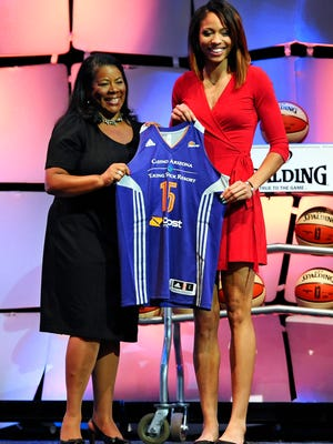 Isabelle Harrison (right) holds up a Phoenix Mercury jersey with WNBA President Laurel J. Richie after the Mercury selected Harrison as the No. 12 pick in the WNBA draft, Thursday, April 16, 2015, in Uncasville, Conn.