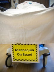 A mannequin on board sign adorns a gurney carrying