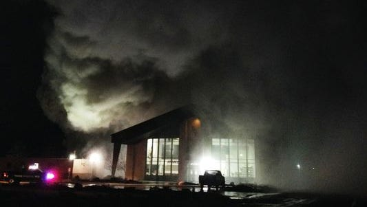 Smoke billows from a fire in a maintenance shop building to the west of the gym that is seen (lighted building) Saturday evening at Rite of Passage-Silver State Academy.