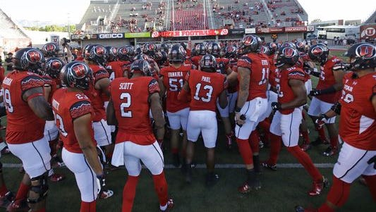 Members of the Utah football team huddle before the start of their NCAA college football game against Utah State Friday, Sept. 11, 2015.