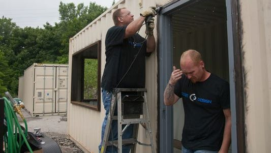 Kyle Gilman (left) with Core Design polishes the welding on a doorway of a kitchen as Jeremy Semones, owner of Core Design, passes through.