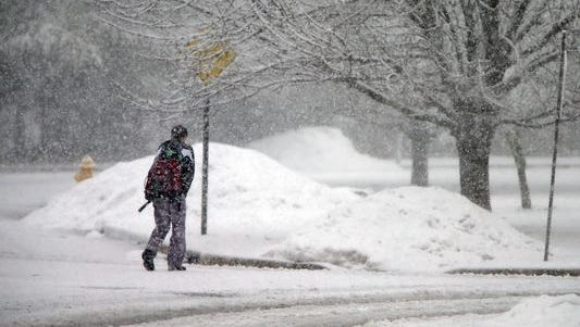 A boy walks along Oak Forest Drive in Brick during Friday's snow fall.