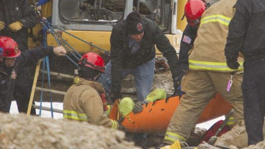 Firefighters and special response personnel lift a worker from a ditch in front of the Livingston County Courthouse where the worker had become partially buried Friday morning.