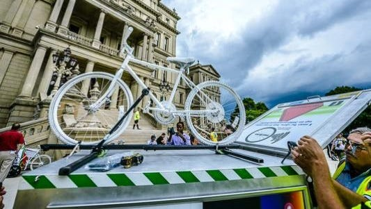 """A """"Ghost Bike"""" is secured to a trailer to be pulled during a Ride of Silence memorial tribute bicycle ride honoring Randy Robinson, of St. Johns, who died after a crash with a motor vehicle outside of Grand Ledge and in honor of nine cyclists killed or injured near Kalamazoo on June 7."""