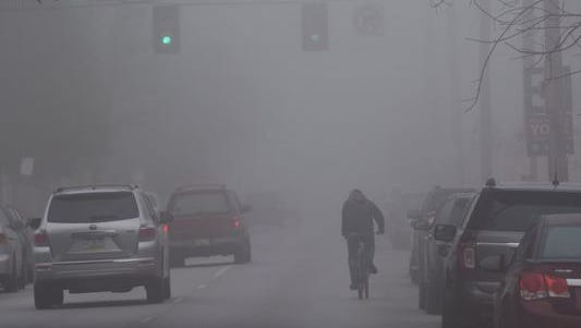 A bicyclist rides through fog in downtown York in this 2016 file photo.