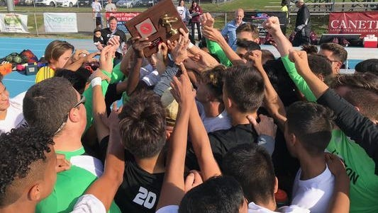 Clifton players holding up the Mustangs' 20th Passaic County title trophy after a 2-1 win over Passaic High School.