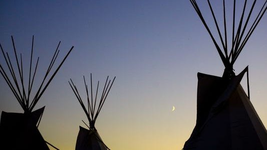 A crescent moon rises between lodges during the Kul Wicasa Pow Wow in Lower Brule, S.D.