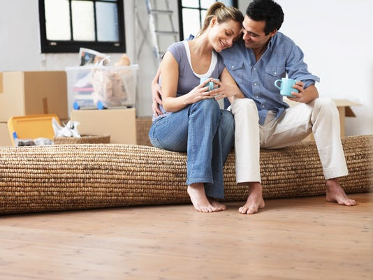 Couple embracing, sitting on mat indoors, smiling