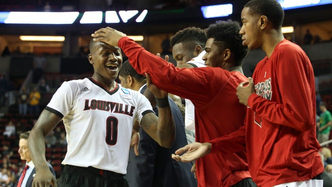 U of L's Terry Rozier, #0, left, is congratulated by teammate Anton Gill, #1, after defeating Northern Iowa at the KeyArena in Seattle during the third round of the NCAA tournament.March 22, 2015
