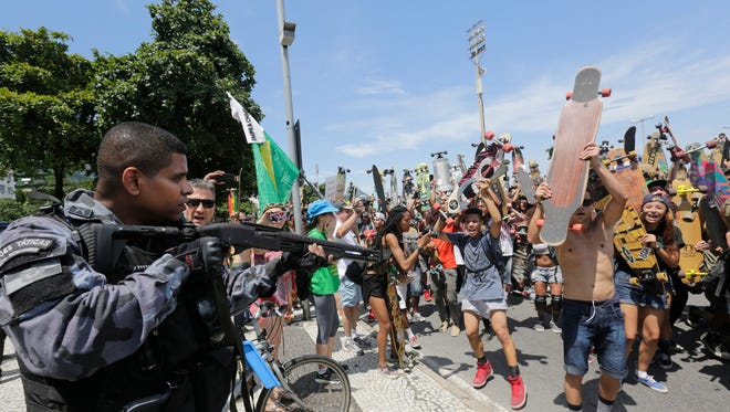 A police officer aims his gun, armed with rubber bullets, toward a group that argued with demonstrators of a march for the impeachment of Brazilís President Dilma Rousseff, on Copacabana beach, Rio de Janeiro, Brazil, Sunday, Dec. 13, 2015.