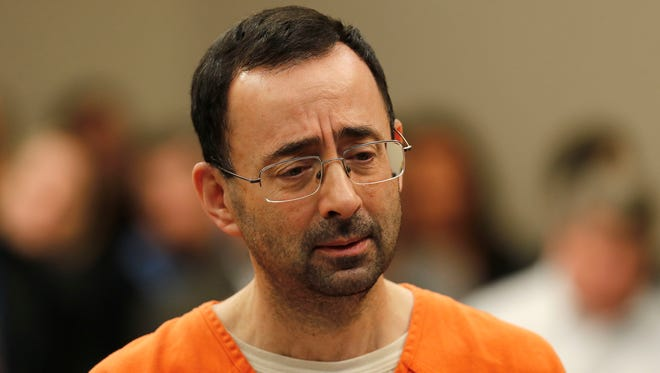 Dr. Larry Nassar appears in court for a plea hearing in Lansing, Mich.