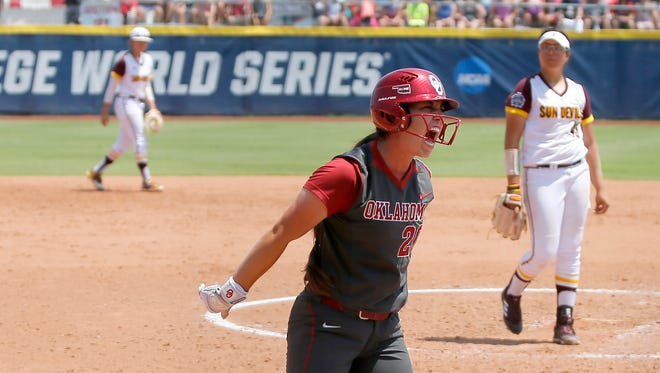 Oklahoma's Caleigh Clifton (20) celebrates after getting walked in the fourth inning of an NCAA softball Women's College World Series game in Oklahoma City, Saturday, June 2, 2018.