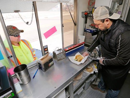 Owner Jose Alfonso Lopez serves up steak tacos for