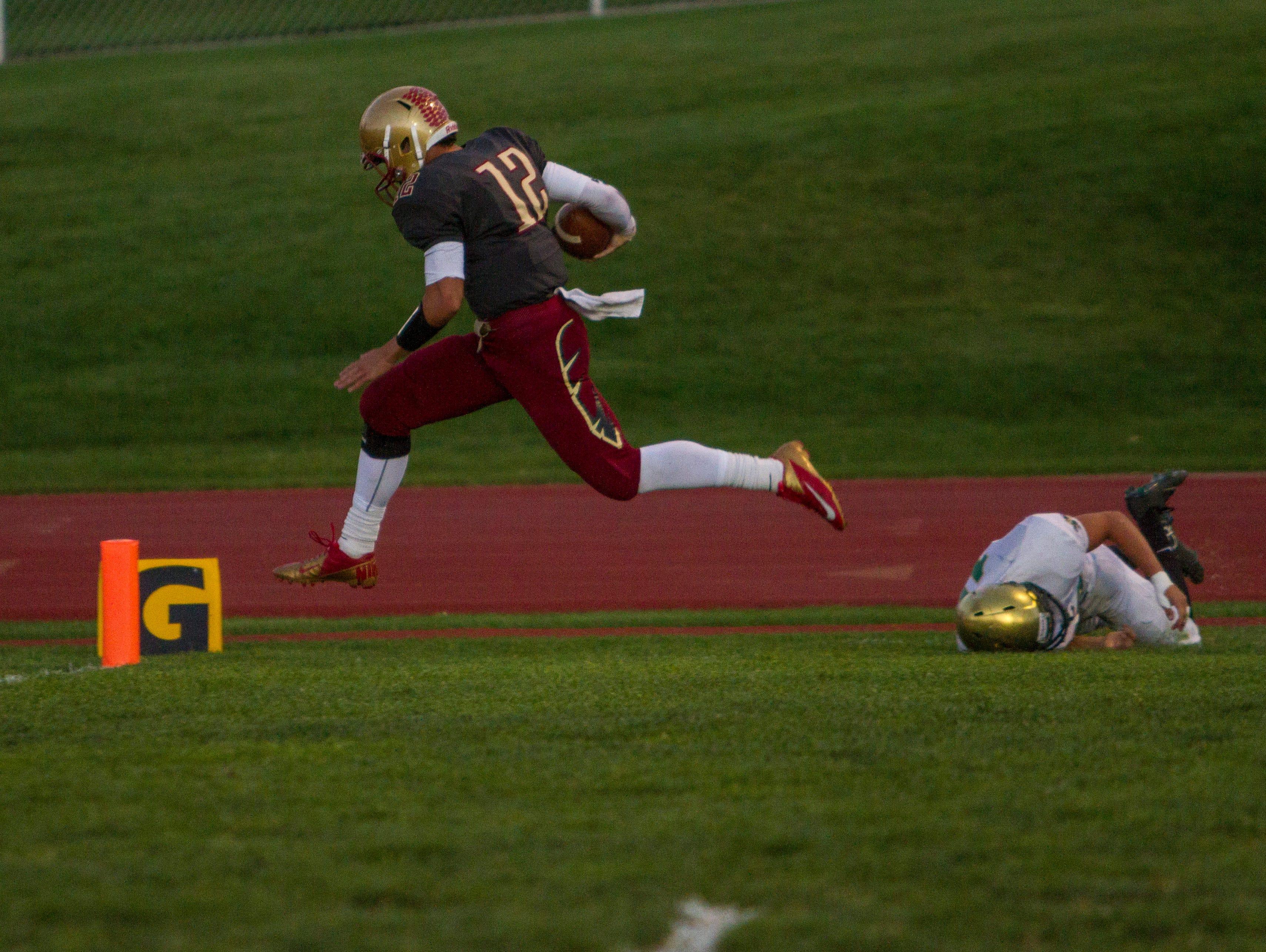 Cedar's Mason Fakahua (#12) runs for a touchdown against Snow Canyon, Friday, Sept. 25, 2015.