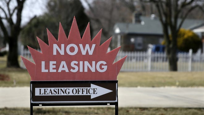 "A ""now leasing"" sign sits outside an apartment complex."