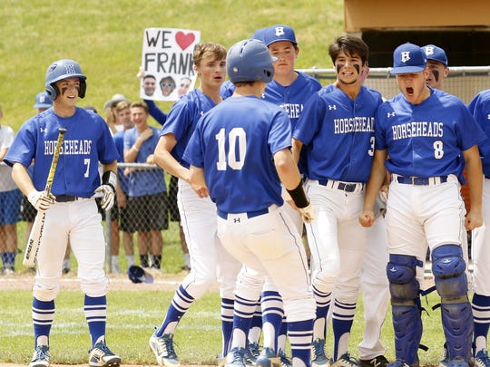 Frank Wayman Jr. (10) is greeted by teammates after