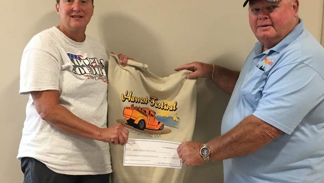 Nancy Hutchinson (left), the Adopt-A-Soldier Door County founder, was honored by the state Assembly Thursday as a Hometown Hero. Hutchinson is pictured here, with Russ Gilman, accepting a check for $1,400 from Old Bolts Car Club in 2016.