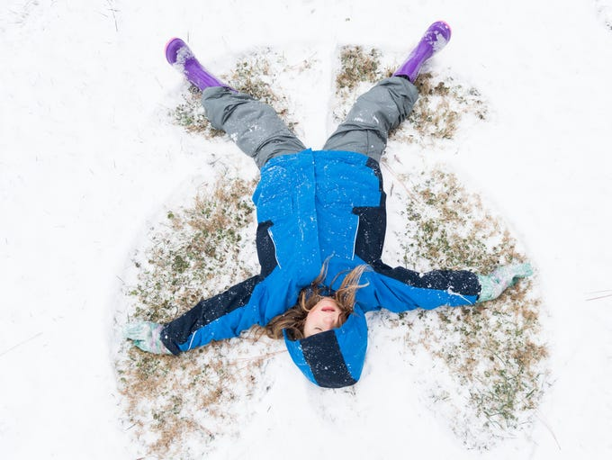 Kayden Randolph creates a snow angel while playing