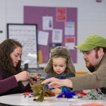 Bree Nash of Ithaca and her 2-year-old daughter Kate get a lesson in fly tying from her brother-in-law, Colin Nash of Wolcott, at the 23rd annual Ithaca Fishing Day on Saturday at Boynton Middle School. Colin Nash is a native of Slaterville and an experienced local fisherman.