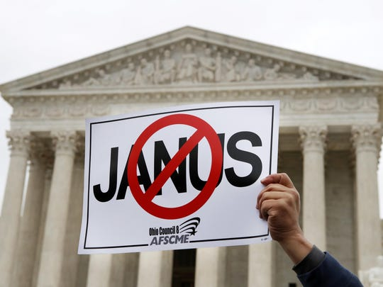 Stephen Roberts, with the American Federation of State, County and Municipal Employees (AFSCME), holds up a sign against Mark Janus during a rally outside of the Supreme Court, Monday, Feb. 26, 2018, in Washington.