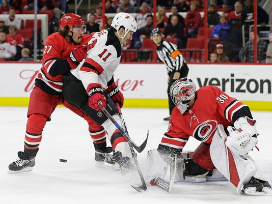 Carolina Hurricanes' Justin Faulk (27) and goalie Cam Ward (30) block New Jersey Devils' Brian Boyle (11) during the first period of an NHL hockey game in Raleigh, N.C., Friday, March 2, 2018. (AP Photo/Gerry Broome)