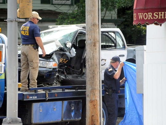 State police officials prepare to cover the patrol car of Millville Police Officer Christopher Reeves who was killed in an automobile accident in New Jersey on July 8, 2012.