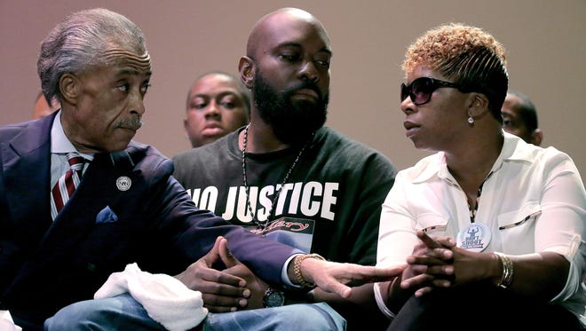 Al Sharpton speaks with the parents of Michael Brown, Michael Brown Sr. and Lesley McSpadden, during a rally at Greater Grace Church in Ferguson, Mo.
