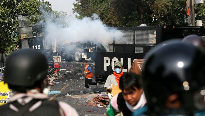 Anti-government protesters run for cover after police fire tear gas during a protest rally in Bangkok Tuesday.