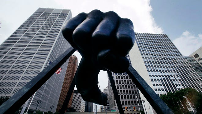 """In this July 18, 2013 file photo, the Detroit skyline rises behind the Monument to Joe Louis, also known as """"The Fist""""."""