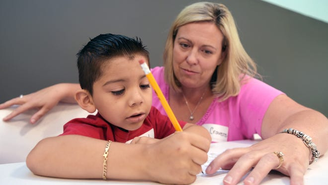 """Franklin Special School District teacher Danette Cravens helps Alex Martinez, 5, with writing his name during a three-day """"Get Ready for Kindergarten"""" class at the Franklin Estates mobile home community."""