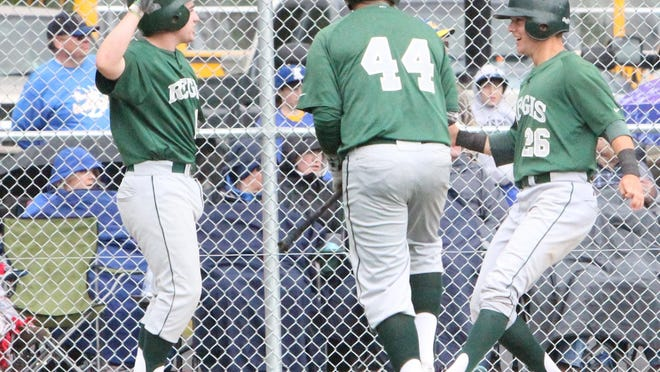Regis' Casey Dailey (left) welcomes Tim Frith (right) to home plate in the third inning as they gave the Rams a 2-0 lead against Knappa on Tuesday, June 2, 2015.