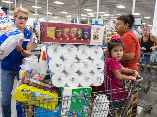 Cashier Karen Haggard, left, helps check out an overflowing cart for Bonita Springs resident Simona Magellan's and her daughter Victoria Marine, age 3, on Tuesday, September 5, 2017. Monday, Florida Gov. Rick Scott issued a state of emergency for the state of Florida.
